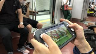 A passenger uses a Nintendo Switch to play video game 'Animal Crossing: New Horizons' on a subway train of Beijing Subway Line 1 on June 14, 2020 in Beijing, China.